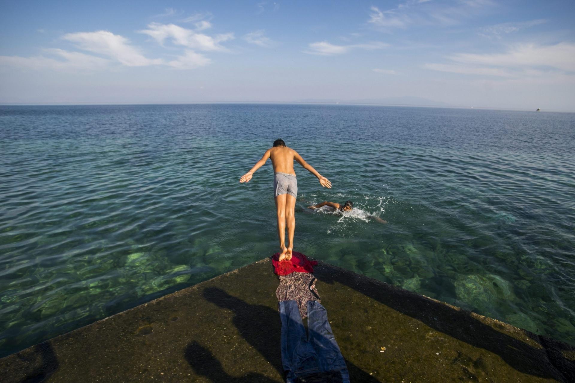 5.out.2015 - Refugiado mergulha no Mar Mediterrâneo no porto de Mitilene, na ilha grega de Lesbos. Segundo a Guarda Costeira do país, cerca de cem mil refugiados chegaram à costa grega só em agosto de 2015