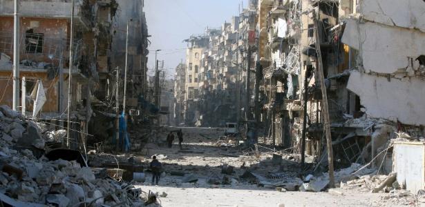 Sírios caminham entre prédios destruídos na região de Aleppo