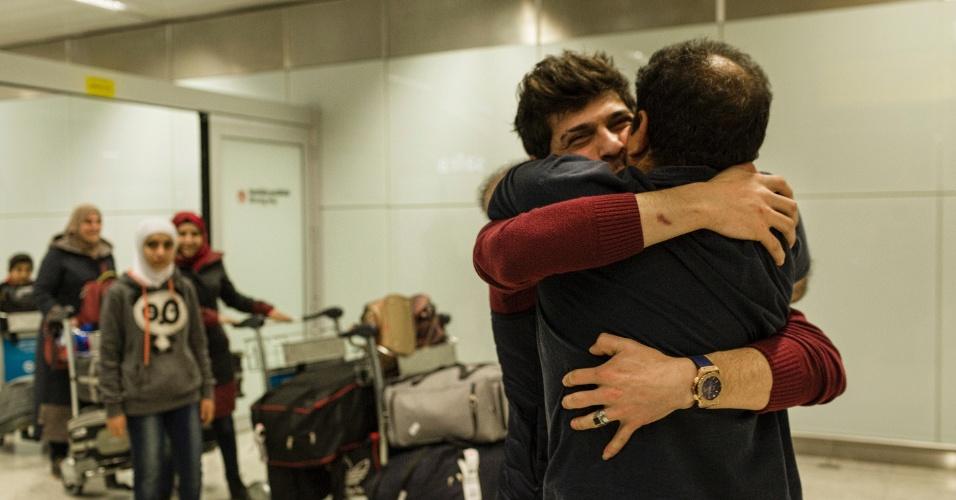 13.mar.2017 - O refugiado sírio Adnan Alkhaled abraça o filho, Mohammed, na chegada de sua família ao país no aeroporto de Cumbica
