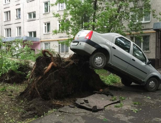 Carro fica preso sobre tronco partido de árvore após temporal em Moscou, Rússia