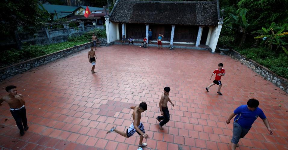19.maio.2018 - Crianças jogam futebol com bola de plástico em um templo na vila Hoang Xa, no Vietnã