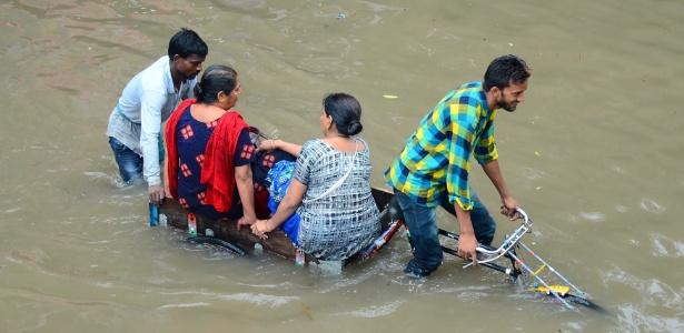 Mulheres indianas são transportadas por uma bicicleta em uma rua inundada em Mathura, no estado de Uttar Pradesh, após fortes chuvas caírem sobre a região - AFP