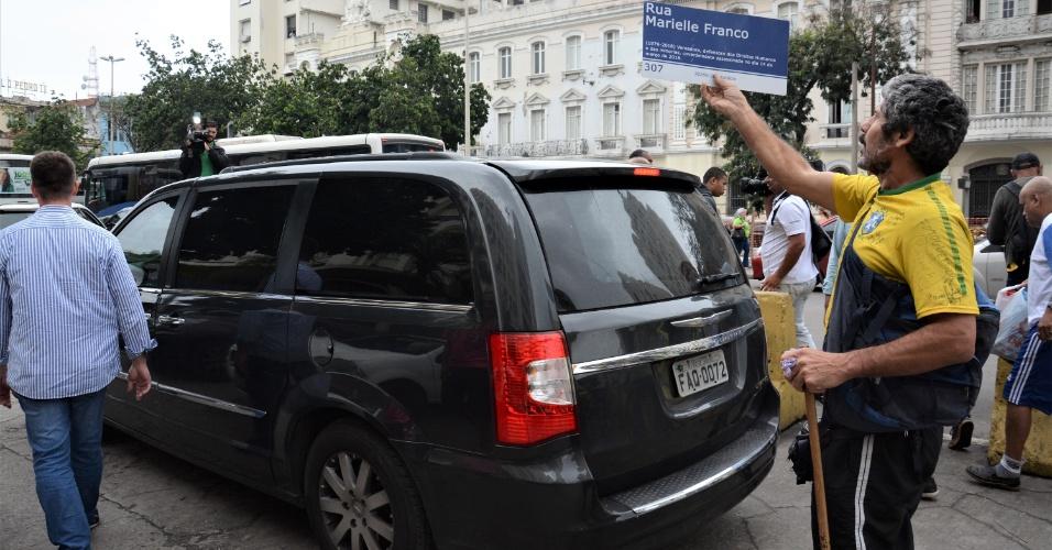 29.out.2018 - Governador eleito do Rio, Wilson Witzel (PSC), toma café e conversa com eleitores na estação Central do Brasil, no centro da capital. Um manifestante levanta placa em homenagem à vereadora Marielle Franco, morta em março, como protesto