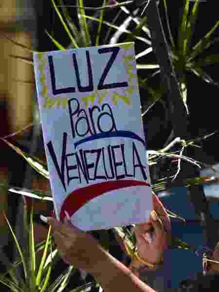 """Mulher segura um cartaz escrito """"Luz para Venezuela"""" durante uma manifestação de oposição em Caracas - Yuri Cortez/AFP"""