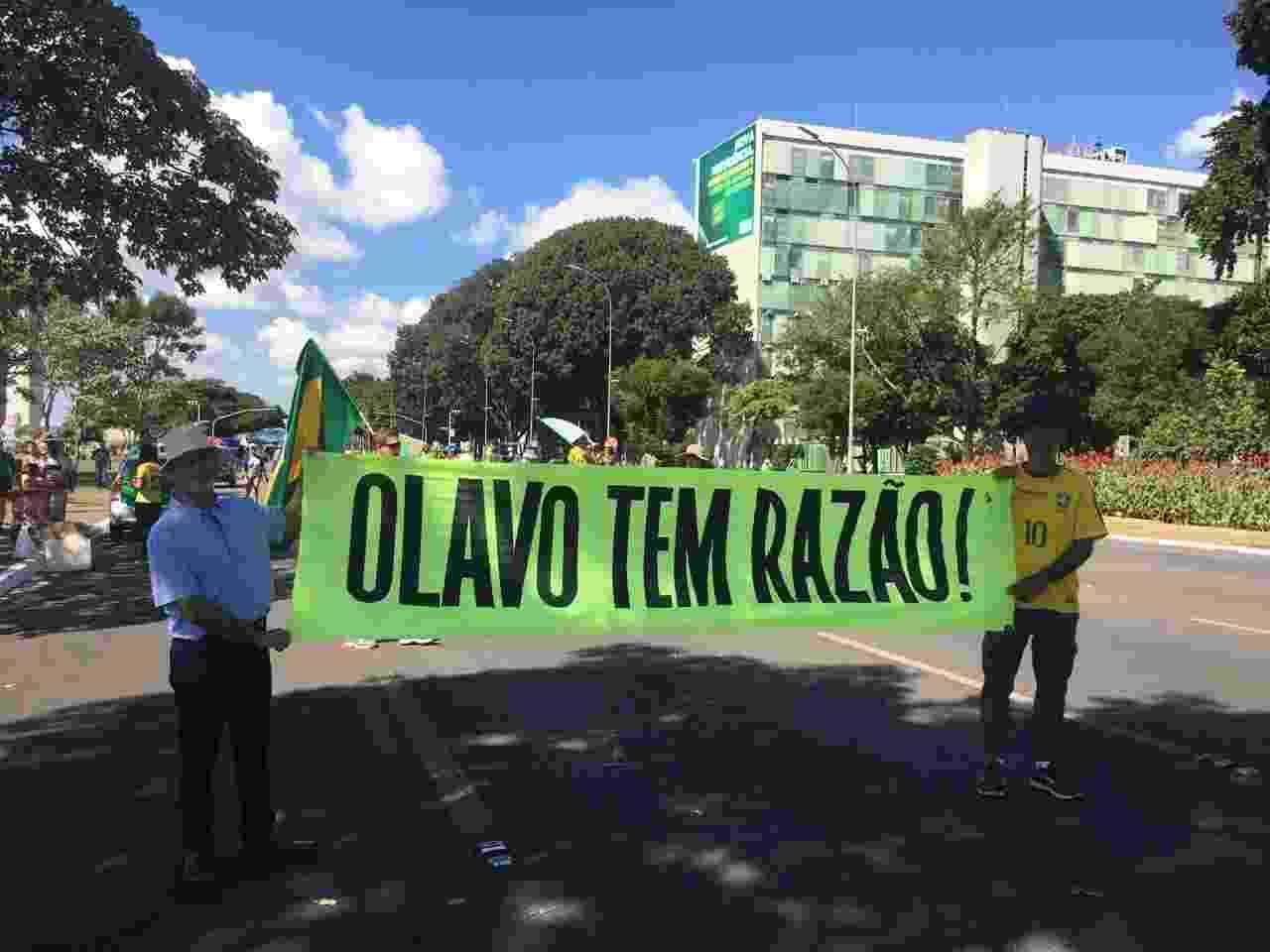 26.mai.2019 - Médico Armando José (à esquerda) carrega faixa em referência ao escritor Olavo de Carvalho, guru do presidente Jair Bolsonaro (PSL), em Brasília - Hanrrikson de Andrade/UOL