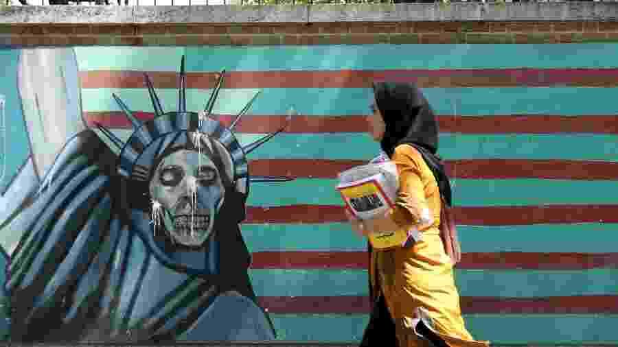 22.jun.2019 - Em Teerã, capital do Irã, mulher passa em frente a pintura no muro da antiga embaixada dos EUA. A pintura retrata a Estátua da Liberdade como uma caveira - Atta Kenare/AFP