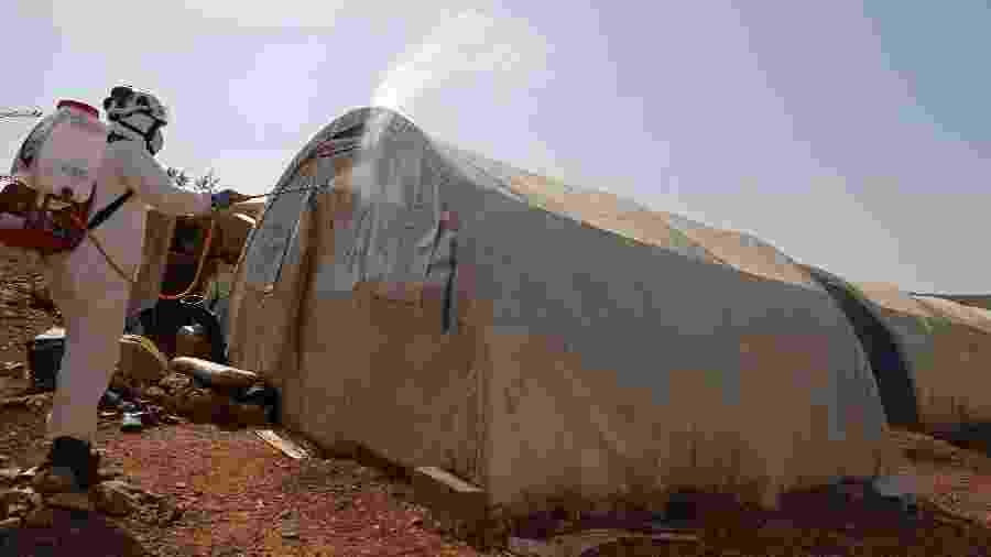 24.mar.2020 - Integrante da defesa civil da Síria desinfeta barraca no campo de refugiados de Kafr Lusin - AAREF WATAD / AFP