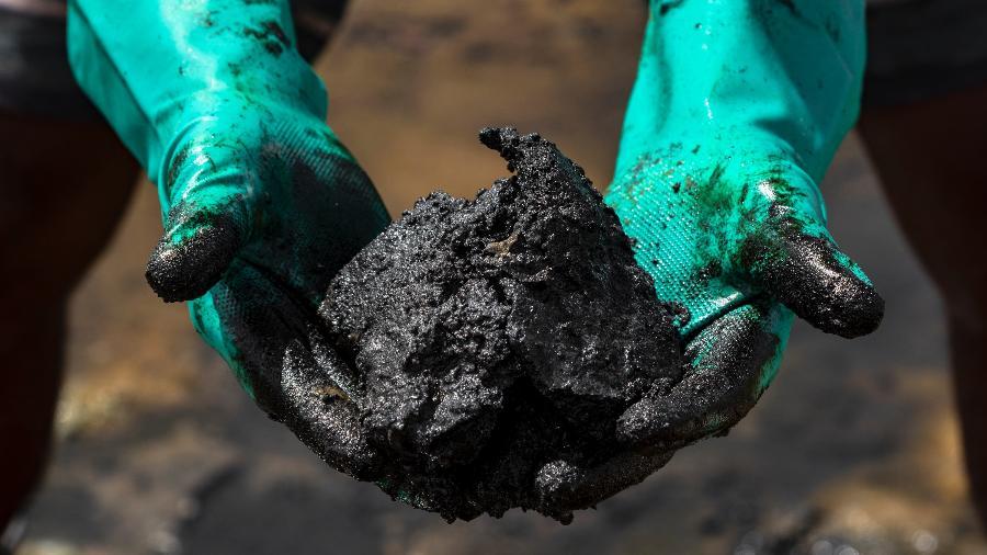 Voluntários retiram petróleo na praia de Itacimirim (BA), em março deste ano - Mateus Morbeck/UOL