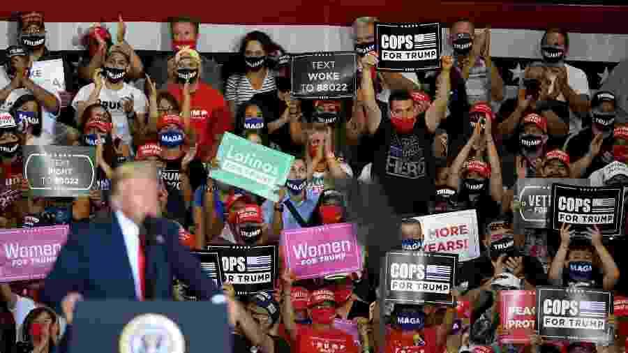 13.set.2020 - Apoiadores do presidente Donald Trump seguram cartazes enquanto o republicano discursa em evento de campanha em Henderson, Nevada - Ethan Miller/Getty Images/AFP
