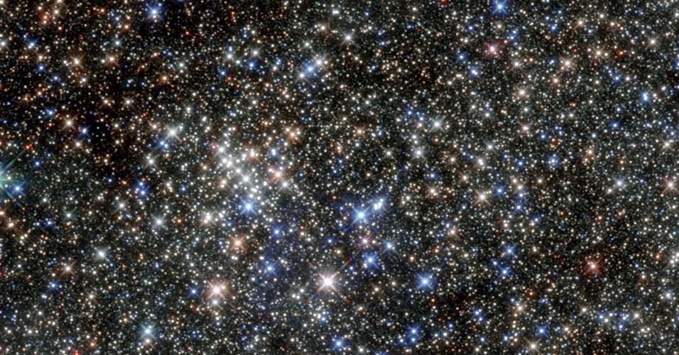 17.jul.2015 - Este conjunto de estrelas recebeu seu nome de Quintuplet Cluster devido a suas cinco estrelas mais brilhantes, mas é praticamente impossível identifica-las no meio de outras milhares. O aglomerado está localizado apenas a 100 anos-luz do centro de nossa galáxia. A proximidade das estrelas com a poeira do centro da galáxia faz com que grande parte de sua luz visível seja bloqueada, o que ajudou a mantê-las desconhecidas até 1990, quando foram reveladas por observações com infravermelho. O aglomerado é lar da Pistol Star, uma das estrelas mais luminosas conhecidas na Via Láctea, que está prevista para virar uma supernova em três milhões de anos. A presença das estrelas supergigantes vermelhas indicam que o aglomerado tem quase quatro milhões de anos