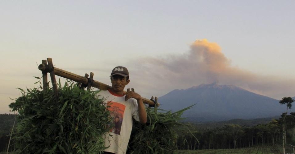 23.jul.2015 - Agricultor caminha por um pasto enquanto o vulcão Raung, no leste de Java, na Indónesia, expele fumaça. As erupções do vulcão nas últimas semanas forçou o fechamento de vários aeroportos no país