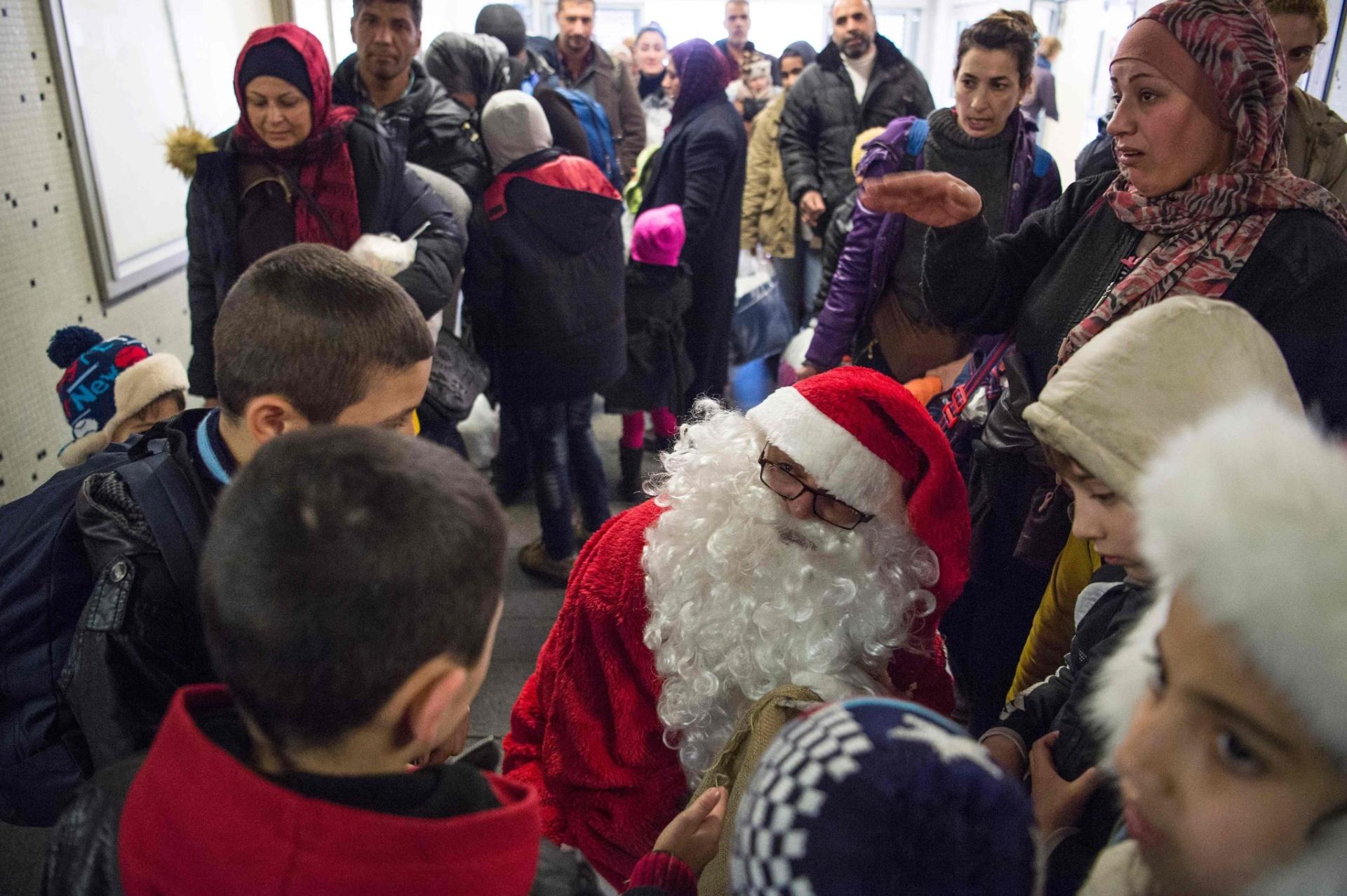 24.dez.2015 - Voluntário vestido de Papai Noel distribui presentes para filhos de refugiados que permanecem na estação de trem Schoenefeld, perto de Berlim, na Alemanha, antes de serem enviados a acampamentos