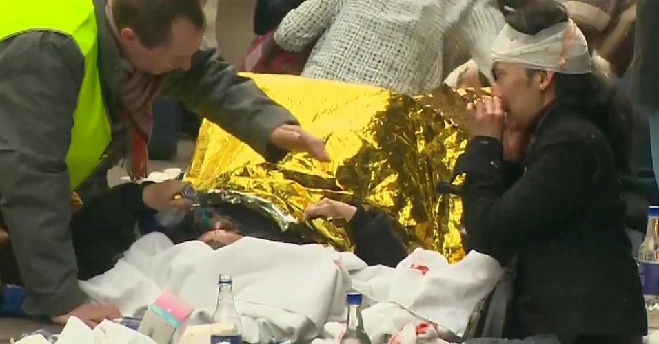 22.mar.2016 - Vítimas são socorridas do lado de fora da estação de metrô Maalbeek, em Bruxelas, um dos alvos dos atentados terroristas coordenados que atingiram a Bélgica na manhã desta terça-feira