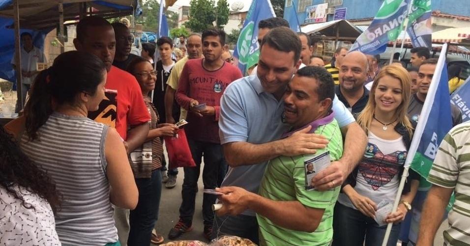 1º.out.2016 - Flávio Bolsonaro, candidato a prefeito do Rio de Janeiro pelo PSC, conversa com eleitores em uma feira em Sepetiba, zona oeste do Rio de Janeiro