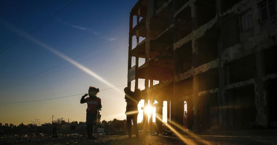 8.nov.2016 - Crianças palestinas passam junto a edifícios destruídos durante a guerra de 50 dias entre Israel e os militantes do Hamas durante o verão de 2014 em Beit Hanun, na Faixa de Gaza