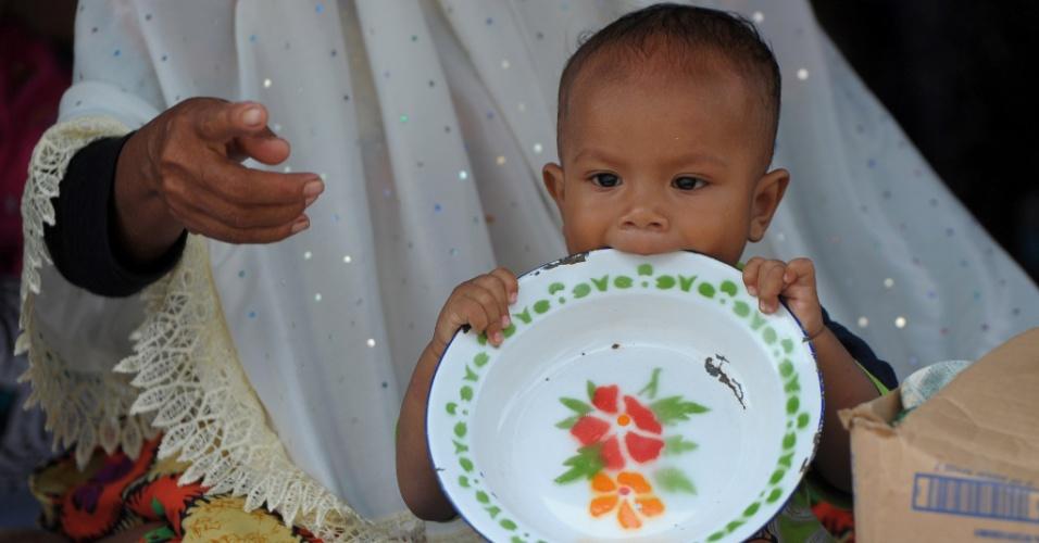 12.dez.2016 - Criança segura um prato na fila com pessoas deslocadas para sua refeição em um abrigo após terremoto de magnitude 6.5 em Pidie Jaya, província de Aceh, na Indonésia