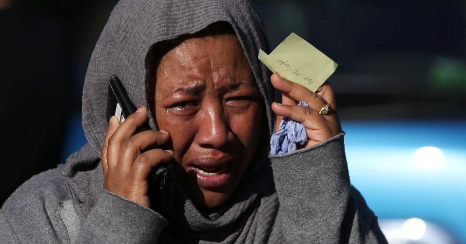 14.jun.2017 - Mulher chora enquanto tenta localizar parente que está desaparecido e que mora na torre Grenfell