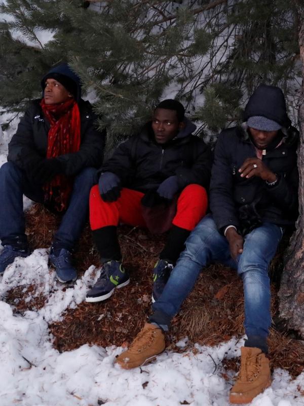Imigrantes descansam após cruzar parte dos Alpes, na tentativa de chegar ao lado francês