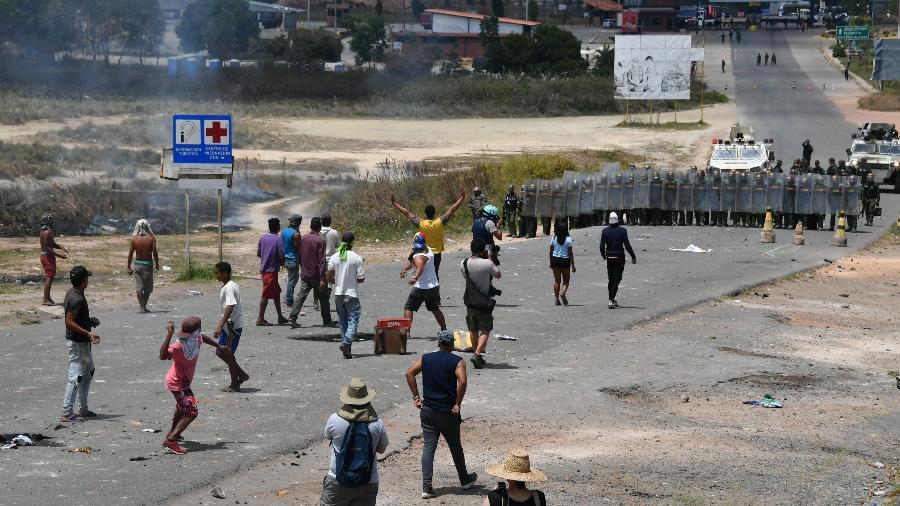 24.fev.2019 - Manifestantes atiram pedras contra membros da Guarda Nacional Bolivariana na fronteira entre Venezuela e Brasil, em Pacaraima, Roraima - Nelson Almeida/AFP