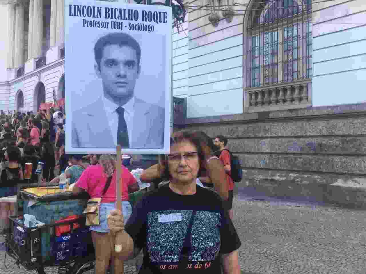 31.mar.2019 - Na Cinelandia, a dentista Tânia Roque, 72, ostentava um cartaz de seu marido, o sociólogo e professor Lincoln Bicalho Roque, torturado e morto pelo regime em 1973. Ato no centro do Rio marcou o repúdio ao golpe de 1964 - Marina Lang/UOL