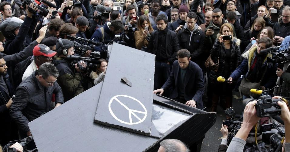 """14.nov.2015 - Um homem que não foi identificado fez uma homenagem emocionante diante do Bataclan, um dos cenários dos atentados terroristas de sexta-feira (13) em Paris. Ele montou um piano e tocou """"Imagine"""", o hino pacifista composto pelo beatle John Lennon. Em seguida, se retirou"""