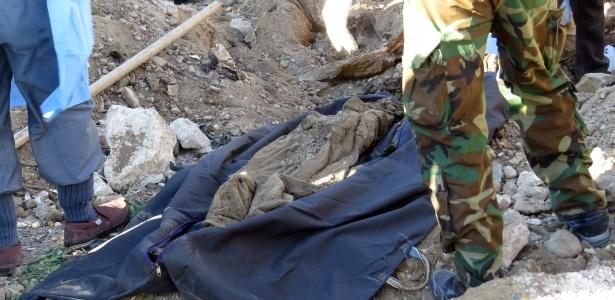 Forças de segurança iraquianas recolhem restos mortais encontrados em uma cova comum em Ramadi