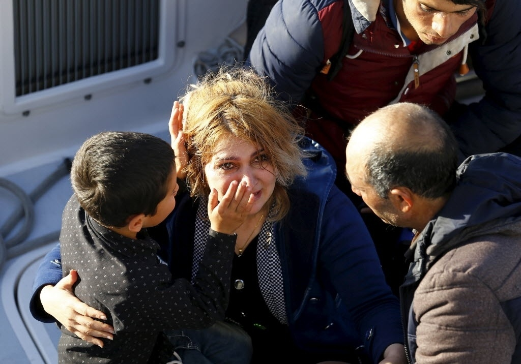 29.fev.2016 - Menino refugiado enxuga lágrimas de sua mãe enquanto ambos esperam para embarcar em um navio que os levará para Guarda Costeira da Turquia. A família passou por uma tentativa frustrada de travessia quando tentavam chegar a ilha grega de Chios