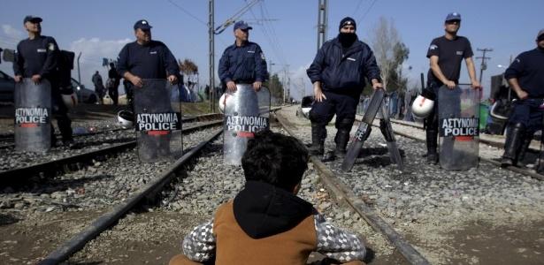 1º.mar.2016 - Menino senta em frente a bloqueio policial na fronteira Grécia-Macedônia