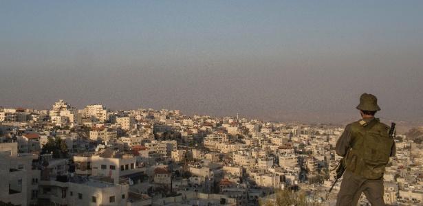 17.out.2015 - Soldado israelense observa bairro palestino em Jerusalém Oriental