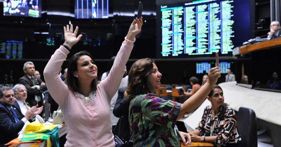 16.abr.2016 - A deputada Mariana Carvalho (PSDB-RO) (à esq.) faz imagens da sessão de discussão do processo de impeachment da presidente Dilma Rousseff no plenário da Câmara, em Brasília