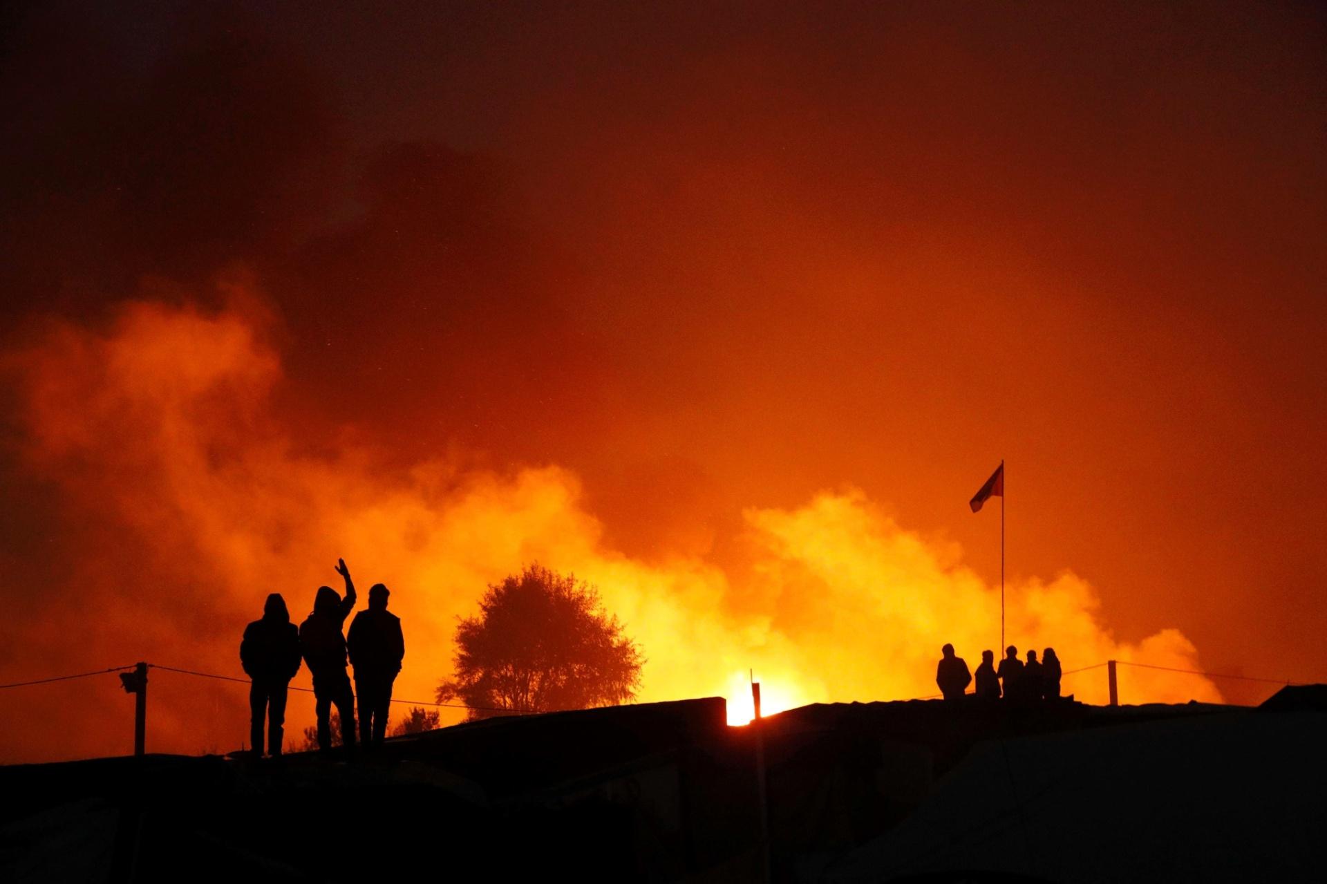 25.out.2016 - Silhuetas de migrantes são vistas perto de chamas no segundo dia de evacuação de refugiados do campo de Calais, na França