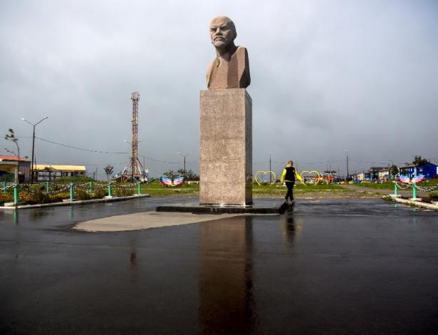 Mulher passa por estátua de Vladimir Lênir em Yuzhno-Kurilsk, na ilha de Kunashir, uma das ilhas Curilas