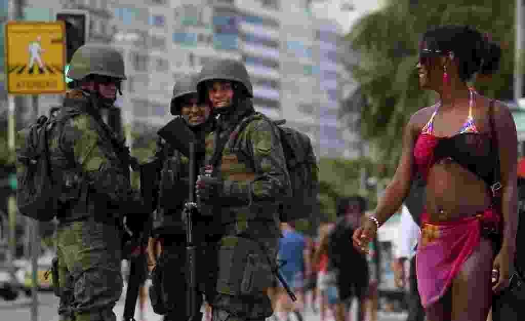 14.fev.2017 - Soldados observam mulher enquanto fazem patrulha na praia de Copacabana, no Rio de Janeiro - Sergio Moraes/Reuters