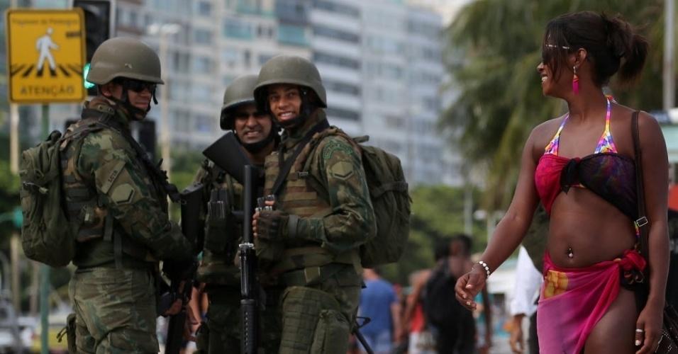 14.fev.2017 - Soldados observam mulher enquanto fazem patrulha na praia de Copacabana, no Rio de Janeiro