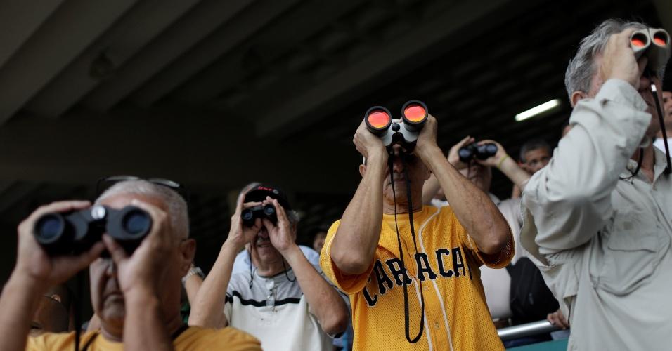 Homens observam corrida de cavalos no Hipódromo La Rinconada, em Caracas, Venezuela