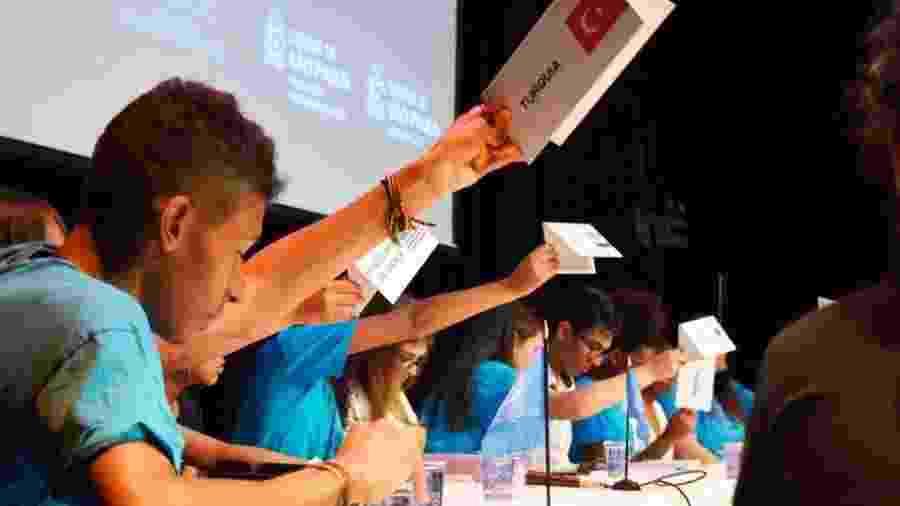 """Jovens erguem os cartazes de """"seus"""" países para sinalizar que querem se manifestar, em sessão que simula uma assembleia da ONU em escola da Cidade Tiradentes - Divulgação/Secretaria Municipal de Educação de São Paulo"""
