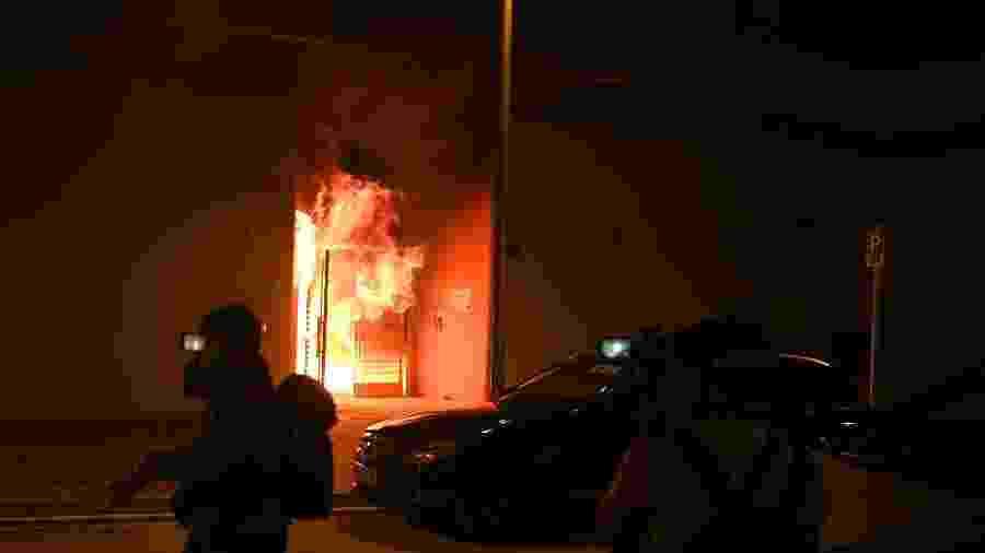 A entrada de conjunto habitacional é incendiada durante protestos contra os planos da propriedade ser usada como campo de quarentena - Philip Fong/AFP