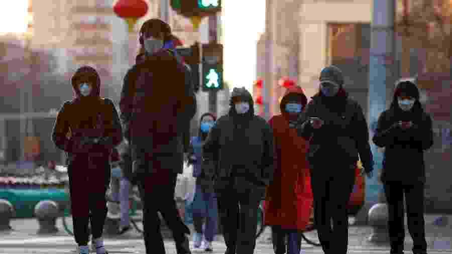 Pessoas com máscara de proteção em rua de Pequim, na China - THOMAS PETER