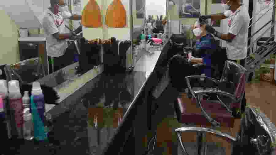 Barbearia adota uso de máscara e plásticos nos assentos para atender clientes durante pandemia do coronavírus - Fernando Frazão/Agência Brasil