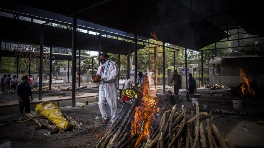 Um homem realiza a última cerimônia para sua esposa, que morreu de covid-19. Casos da doença estão saindo do controle na Índia, com infecções diárias chegando a 300.000 - Anindito Mukherjee/Getty Images