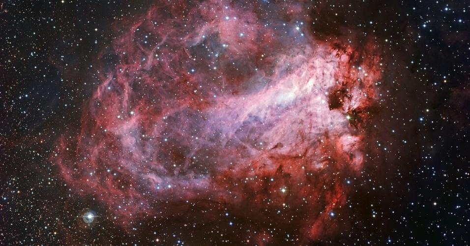 23.set.2015 - NEBULOSA ROSA - Uma nova imagem cor de rosa da região da nebulosa Ômega, conhecida também como Messier 17, foi registrada por um telescópio de mais de dois metros que fica no observatório de La Silla, no Chile. A foto é uma das mais nítidas já registradas da região e mostra toda a nebulosa, revelando seu tamanho total, além de nuvens de gás, poeira e estrelas recém nascidas