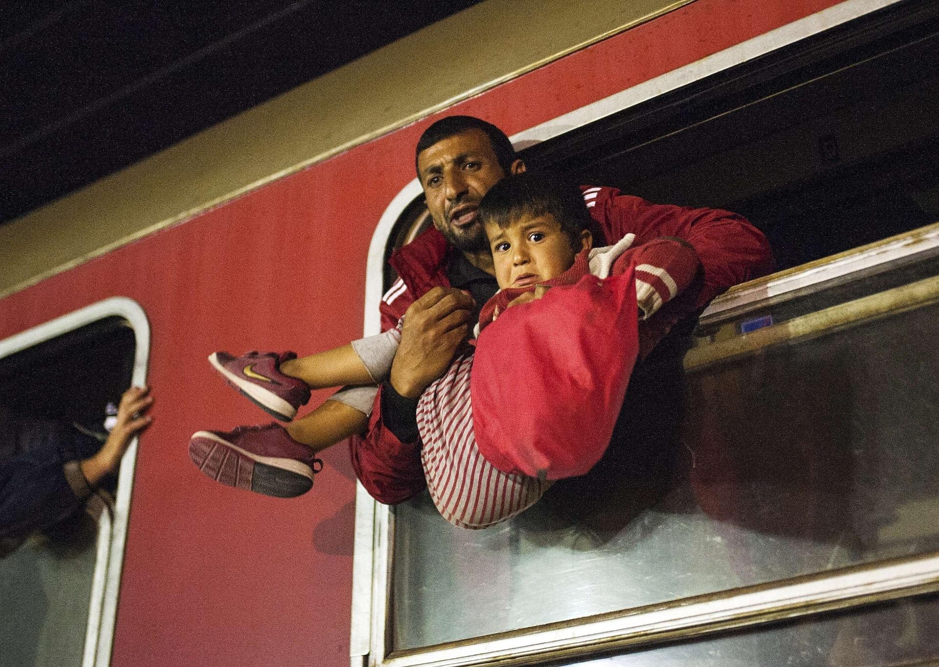 7.out.2015 - Homem segura criança em janela de trem que segue para a Sérvia a partir de Gevgelija, na fronteira entre Grécia e Macedônia. A Macedônia é um país de trânsito crucial na rota de migração de refugiados, muitos deles vindos da Síria, Afeganistão, Iraque e Somália na tentativa de conseguir asilo na Europa