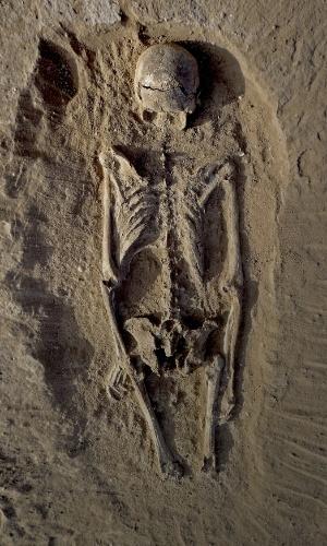 20.jan.2016 - O esqueleto de um homem foi encontrado deitado no sedimento de uma lagoa a 30 km a oeste do Lago Turkana, no Quênia, em um local chamado Nataruk. Ele tinha sinais de múltiplas lesões na parte da frente e no lado esquerdo dele. Cientistas afirmaram que o esqueleto corresponde a evidência mais antiga de uma guerra. O fóssil faz parte de um grupo de pessoas massacradas, mortas por ataques de flecha e lâminas de pedra há cerca de 10 mil anos