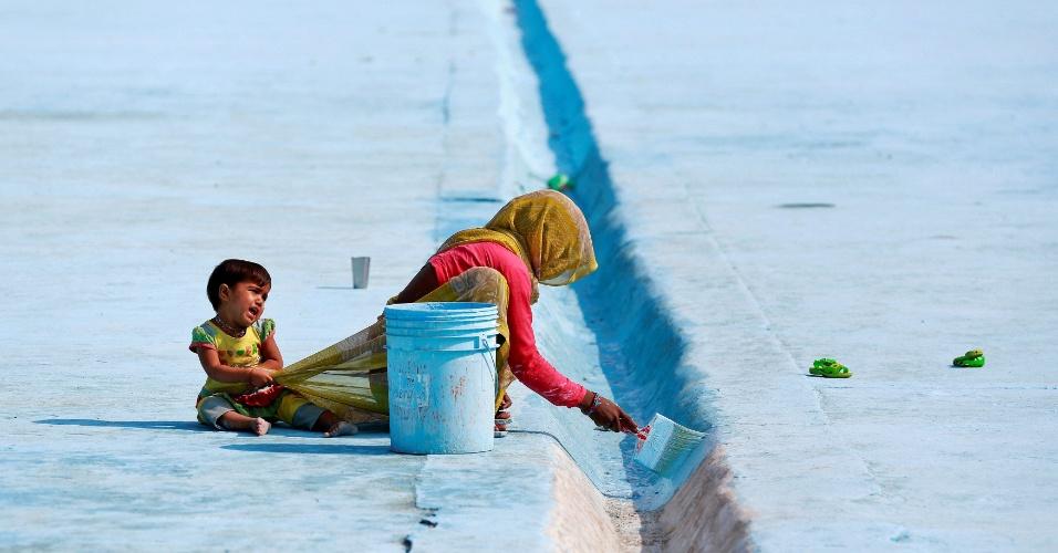 23.nov.2016 - Mulher pinta o chão de um reservatório enquanto sua filha puxa seu saree em Deli, na India
