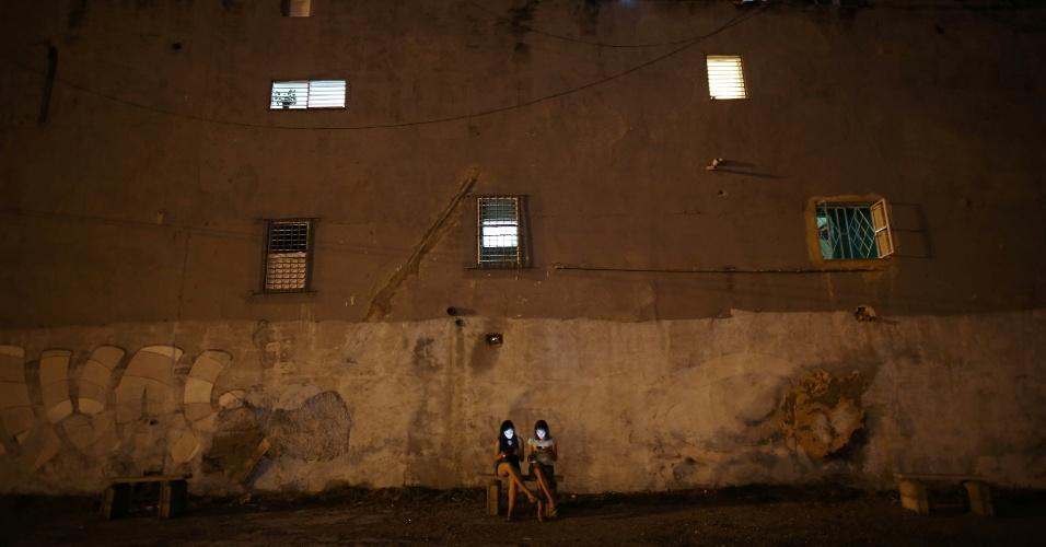 Garotas ficam com os rostos iluminados pelas telas de seus celulares enquanto conectam-se à internet, em Havana