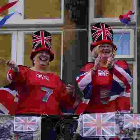 7.mai.2020 - Vestidas com bandeiras do Reino Unido, mulheres homenageiam profissionais do NHS, sistema público de saúde do país - Ian Forsyth/Getty Images