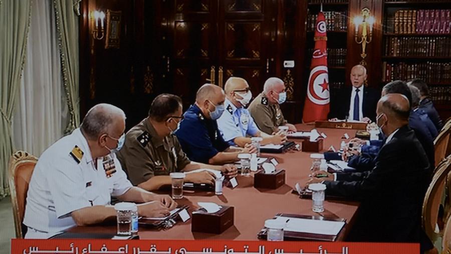 Em imagem da TV estatal, o presidente Kais Saied anuncia dissolução do parlamento e do primeiro-ministro Mechichi, em reunião de emergência com comando militar, no Palácio de Carthage - Fethi Belaid/AFP
