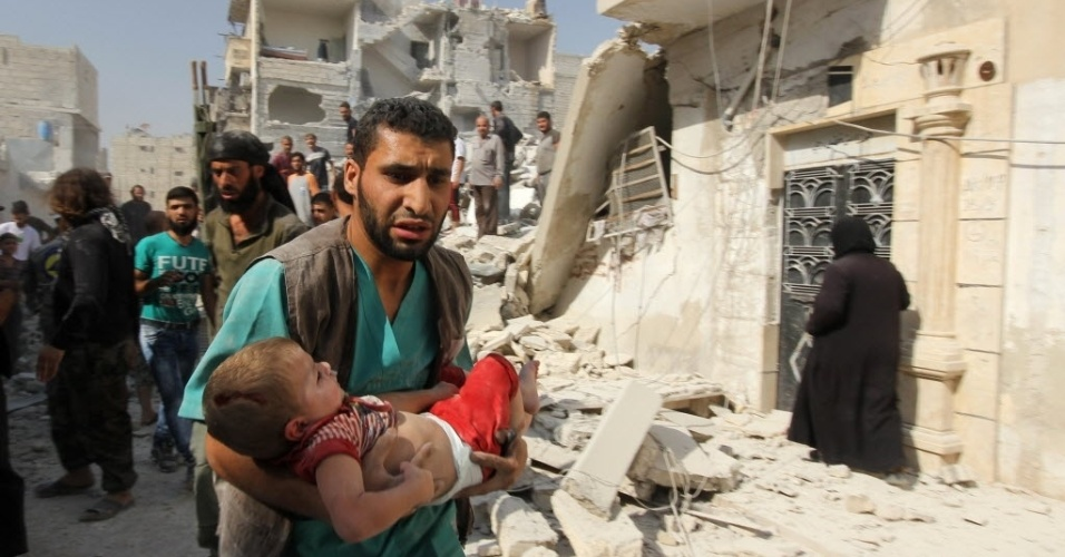 16.set.2015 - Homem carrega criança ferida em um ataque aéreo do governo sírio no distrito de Al-Maghair da cidade síria de Aleppo. A região é controlada por forças do regime, enquanto os rebeldes estão no leste da cidade
