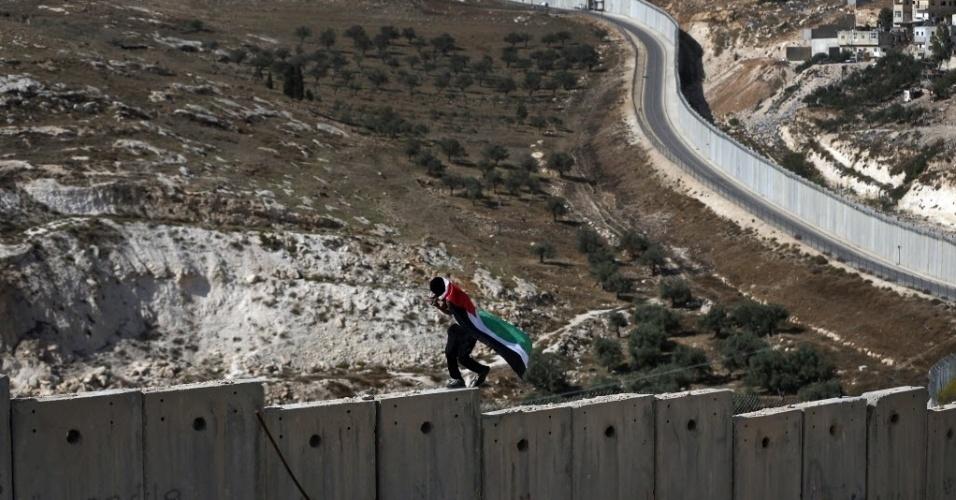 3.nov.2015 - Homem coberto com a bandeira palestina anda sobre o polêmico muro construído pelo governo israelense que separa a cidade de Abu Dis, na Cisjordânia, da parte leste de Jerusalém, em Israel. Palestinos e israelenses vivem confrontos que já causaram dezenas de mortes de ambos os lados e aumentou a violência na região