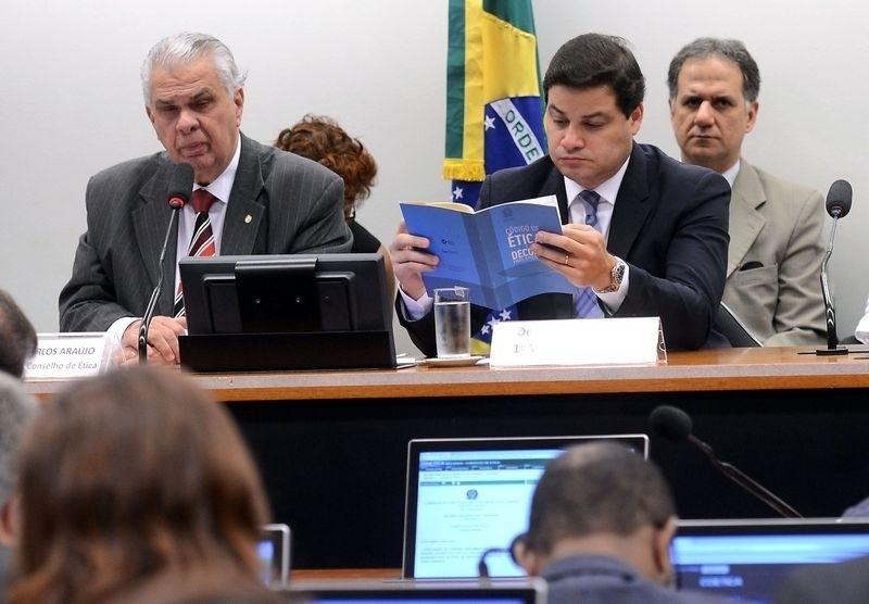 15.dez.2015 - O presidente do colegiado do Conselho de Ética da Câmara, José Carlos Araújo (PSD-BA), à dir., e o deputado Sandro Alex (PPS-PR), com o Código de Ética da Casa nas mãos, participam de sessão que deu continuidade ao processo contra o presidente da Câmara, Eduardo Cunha (PMDB-RJ). Denunciado ao STF (Supremo Tribunal Federal) por suspeita de ter recebido US$ 5 milhões em propina do esquema investigado pela operação Lava Jato, Cunha teve seu nome ligado a contas secretas na Suíça. Ele também foi acusado de mentir à CPI (Comissão Parlamentar de Inquérito) da Petrobras sobre a existência das contas